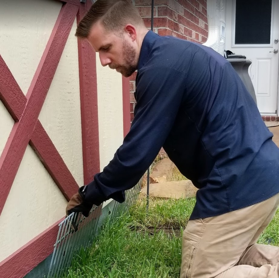 Man putting up small gating to prevent wildlife from getting under shed.