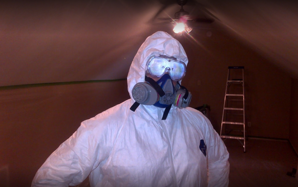 Person wearing insulation mask and body suit in attic.